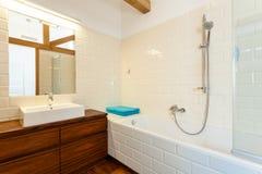 Baño blanco de cerámica y muebles de madera imagen de archivo