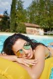 Baño de sol de la mujer joven en piscina del balneario Fotografía de archivo