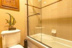 Baño principal en hogar de lujo con la ducha de cristal grande brillante y el cl Imágenes de archivo libres de regalías