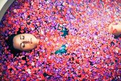 Baño relajante de la mujer con las flores tropicales al aire libre en el hotel de lujo Fotografía de archivo