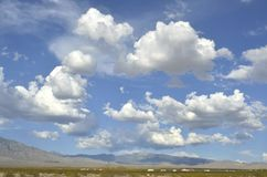 Bałwaniasty biały i szarość chmurniejemy nad pustynia krajobrazem zdjęcie stock