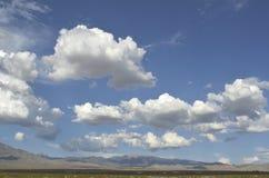 Bałwaniasty biały i szarość chmurniejemy nad pustynia krajobrazem fotografia stock