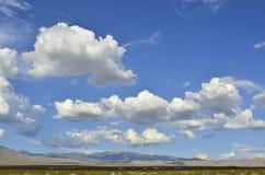 Bałwaniasty biały i szarość chmurniejemy nad pustynia krajobrazem fotografia royalty free