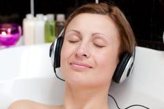 ba泡影听的音乐轻松的妇女年轻人 库存图片