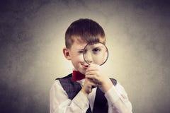 有放大镜的好奇探索的小男孩,在黄色ba 免版税库存照片