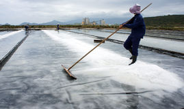 Saltworker gather white grain of salt in pile at s Royalty Free Stock Images