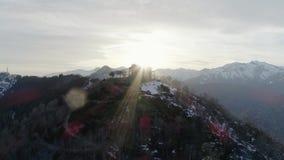 Baan rond de bouw of kerk over de bovenkant van sneeuwberg in de herfst of de winter bij zonsondergang Het bos van het pijnboomho stock videobeelden