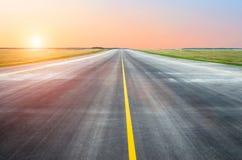 Baanasfalt de luchthaven in de ochtend bij de zonlicht van de dageraadzonsondergang Stock Foto's