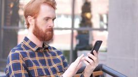 Baard Jonge Mens die Smartphone gebruiken terwijl Openlucht Zitten stock video