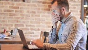 Baard toevallige mens die in schok door resultaten op laptop benieuwd zijn stock video