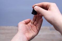 Baard van de mensen de druipende olie in zijn palm van een pipet royalty-vrije stock afbeeldingen