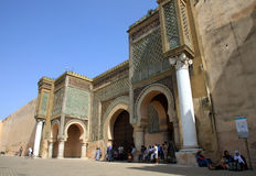 Bab el-Mansour gate. People taking relief from scorching sun in the shadow of the Bab el-Mansour gate decorated with very impressive mosaic ceramic tiles, Meknes Royalty Free Stock Image