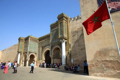 Bab el-Mansour gate and moroccan flag. Moroccan national flag in front of the entrance to the Bab el-Mansour gate decorated with very impressive mosaic ceramic Royalty Free Stock Images