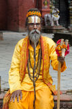 Baba Dressed In Orange. Baba sadu, a saint man, in Nepal, sitting and asking for donation Stock Photos