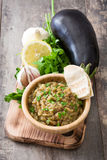 Baba ganoush and ingredients on wooden table Stock Image
