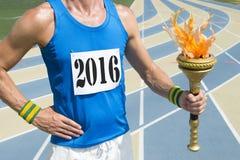 Babador da raça de Wearing 2016 do atleta de trilha que guarda a tocha imagem de stock royalty free
