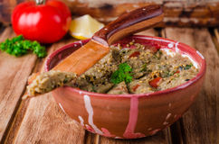 Babaganoush with tomatoes, cucumber and parsley - arabian eggplant dish or salad on wooden background. Selective focus Stock Photo