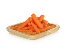 Babay marchewki w drewnianym talerzu na białym tle Zdjęcie Royalty Free