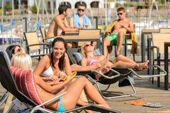 Babbelende meisjes die bij deckchair het zonnebaden liggen Stock Afbeelding