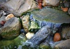Babbling beek met water die over rotsen meeslepen stock fotografie