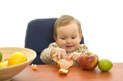 Babby eating fruit Stock Images