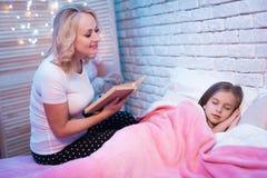 Babci czytelnicza książka podczas gdy wnuczka kłama przy nocą w domu zdjęcia royalty free