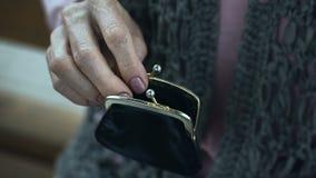 Babci drżącej ręki kładzenia moneta w portflu, emeryta ubóstwo, zbliżenie zdjęcie wideo