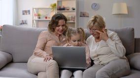 Babci i córki nauczania dziecko używa laptopu zastosowanie, bawić się grę zdjęcie wideo
