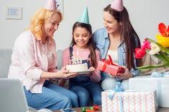 Babci matka i córek urodzinowe siedzące kobiety daje dziewczyna radosna tortowi i teraźniejszości wpólnie w domu zdjęcia stock