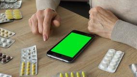 Babci scrolling smartphone app, rozkazuje medycyna online, zieleń ekran zdjęcie wideo