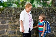 Babcia bierze dziecka, dzieciak chłopiec szkoła na jego pierwszy dniu obraz royalty free