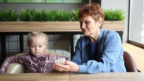 Babcia był ubranym hełmofony jej wnuczka słuchać audio bajka zdjęcie wideo