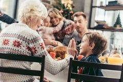 babcia daje wysokości pięć wnuk podczas gdy świętujący boże narodzenia z zamazaną rodziną zdjęcia stock