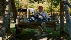 Babcia i dziecko jedziemy na drewnianej huśtawce w parku plenerowym w ranku zdjęcie wideo