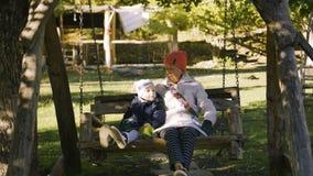 Babcia i dziecko jedziemy na drewnianej huśtawce w parku plenerowym w ranku zbiory wideo