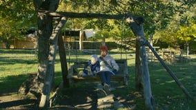 Babcia i dziecko jedziemy na drewnianej huśtawce w parku plenerowym w ranku zbiory