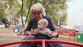 Babcia i dziecko szczęśliwi krążyć carousel w parku w lecie zbiory