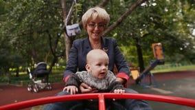 Babcia i dziecko szczęśliwi krążyć carousel w parku w lecie zbiory wideo