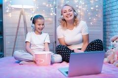 Babcia i wnuczka śmiamy się dopatrywanie film przy nocą w domu zdjęcie stock