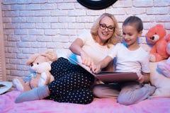 Babcia i wnuczka czytamy lange książkę przy nocą w domu zdjęcie royalty free
