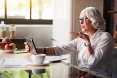 Babcia komunikuje z jej rodziną przez skype Obrazy Stock