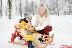 Babcia, niania, matka/stawiamy dalej mitynkę mały dziecko podczas sledding w zima parku obrazy stock
