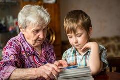 Babcia pokazuje wnuka album fotograficznego rodzina Obrazy Royalty Free