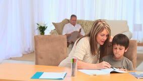 Babcia pomaga jej wnuka robić jego pracom domowym zdjęcie wideo