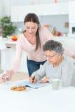 Babcia rozwiązuje crosswords łamigłówkę pomóc pomocy uroczystą córką Zdjęcia Stock