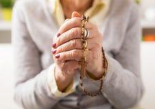 Babcia trzyma drewnianego różana i ono modli się obraz stock
