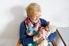 Babcia trzyma nowonarodzonej dziecko wnuka dziewczyny na rękach zdjęcia stock