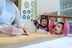 Babcia uczy ona wnuków dlaczego robić makaronowi Obrazy Royalty Free