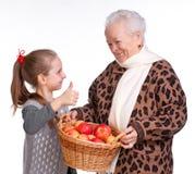 Babcia z wnuczką z koszem jabłka Obrazy Stock