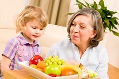 Babcia z wnuczką je owoc w domu Obrazy Stock